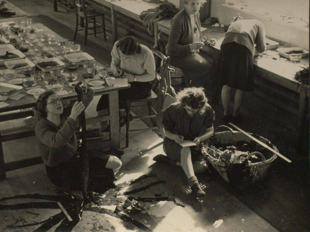 A black and white photograph depicting Knight taking seaweed samples with her students.