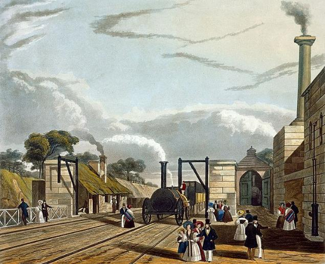 A steam train is stopped at a water-filling station and steam issues from its funnel. People in Victorian dress are standing around; a couple are even on the track in front of the locomotive. To the left is a single storey station station building with a green mossy roof. To the right are more substantial stone buildings with a tall, smoking chimney.