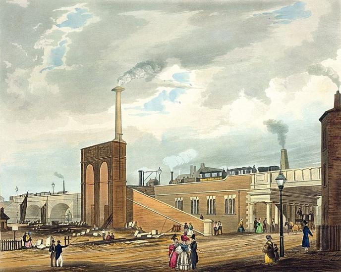 A complex industrial scene showing a street with Victorian figures in colourful dress in the foreground. In the background rise railway buildings. There is a ramp to take goods and people up to a raised railway line and there is a steam train running along the line. To the right is a bridge that goes under the line and to the left is a canal with sailing boats.