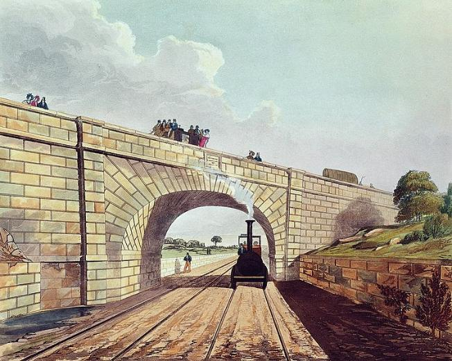 This image has been composed so the viewer seems to be stood on the tracks with a steam locomotive puffing towards them. It is just passing underneath the arch of a bridge which has people looking down, some are sat on a horse-drawn coach. To the right is a stone embankment topped with grass and trees.