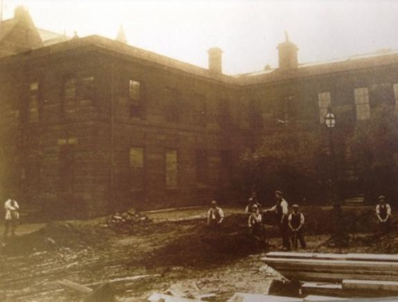 The only surviving photograph of the asylum around 1914 with demolition crew standing in the foreground.