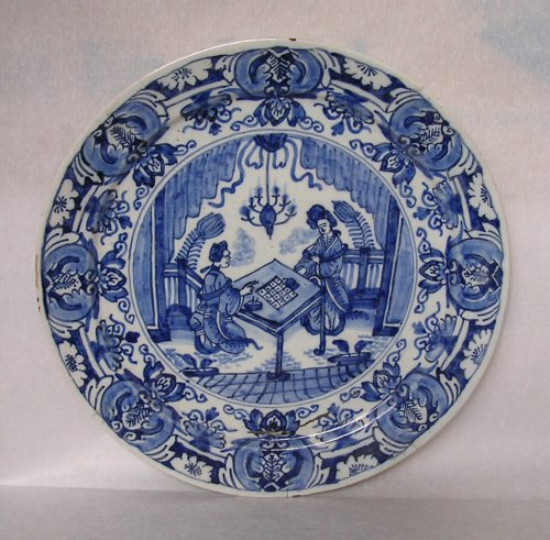 Plate with blue design on white ground. The central part of the plate shows two figures in Chinese-style clothing playing a board game at a table. The figure on the right is standing, while the one on the left is kneeling. Above them hangs a chandelier. There is a repeating floral border round the edge of the plate.
