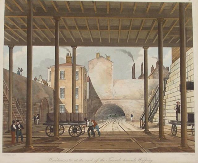 The viewer is inside a warehouse building looking out at railway tracks heading into a tunnel. In the mid-ground, two men push a cart laden with goods towards the left. To the far right, another man stands on an empty cart. Buildings rise above the tunnel with smoking chimneys.