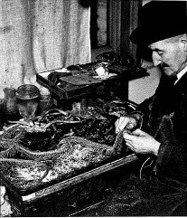 Black and white photograph of a male staff member in a trilby skinning and cleaning a snake skeleton. He sits at a desk which has his tools and other unfinished taxidermy works around him.