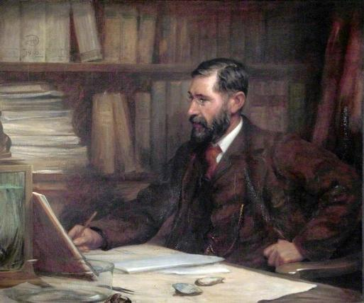 Portrait of a man sat at a desk. He is studying with a book open next to him and some oyster shells to his left. He wears a tweed suit, matching waistcoat, white collar and red tie. He has dark brown hair neatly cut and a beard.He has thin rimmed spectacles on, there is a library of books behind him.