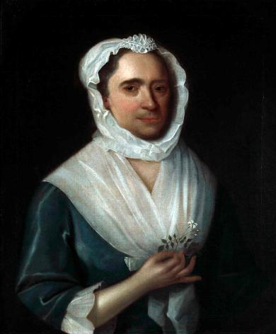 Portrait of a woman wearing a blue silk dress holding a jasmine flower with a white bonnet and collar. She holds a jasmine flower in her right hand. The lower half of her face has a five o'clock shadow.