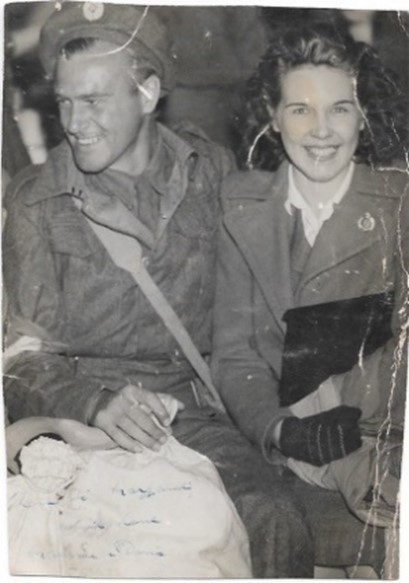 Black and white photograph of Maurice Green and his wife Doris. Maurice is in his uniform they are sat down together, his kitbag across his lap. They are both smiling happy to be reunited.