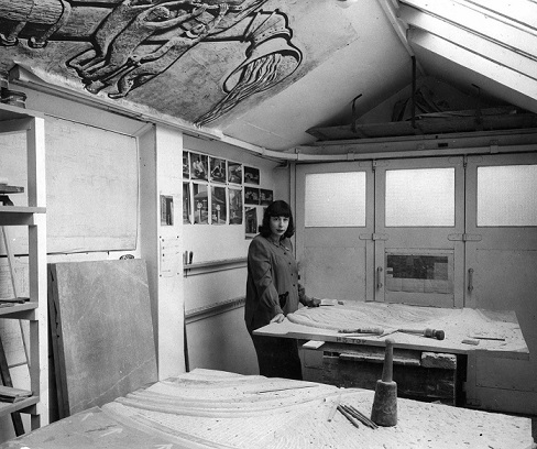Mitzi in her Manchester garage/studio c.1955 working on the Heaton Moor bas relief. On the wall behind her are photos of the sculpture Quickening (©Estate of the Artist)