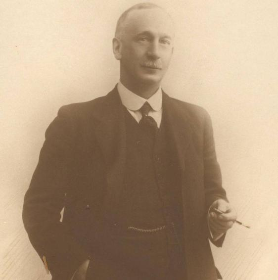 Sepia photograph of the Professor Andrew Melville Paterson.He is dressed in a smart suit, starched round collar and tie. He has a grey moustache and thinning grey hair.He stands with his right had in his pocket, holding a cigarette in a holder in his left hand. He half smiles.