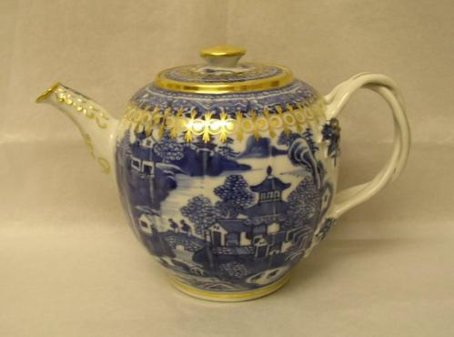 Teapot with lid and twist-style handle. The body has a blue design on white ground with a landscape scene showing pagoda-style buildings and trees set against water. There are two figures on a bridge. The teapot has gilding on the lid, spout and around the top of the body.