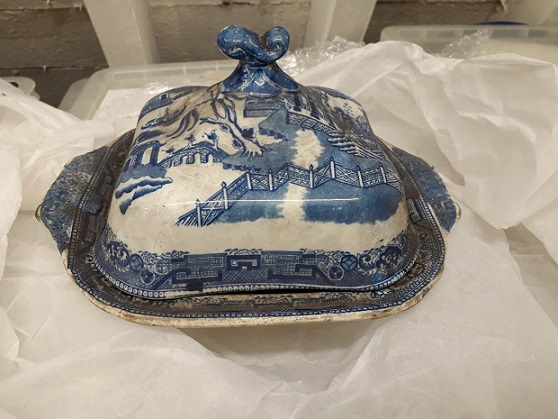 Lipped dish with domed cover in blue and white Willow Pattern design. It is rather dusty. The dish has been photographed on white tissue paper with storage cases in the background.