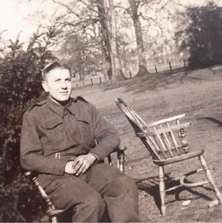 Black and white photograph of William Dickinson Davies sat in profile on a chair, in a garden. He is wearing his uniform, there is a vacant chair next to him.