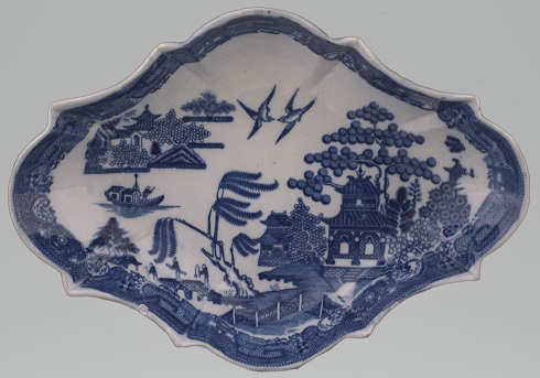 Shallow dish of rhombus shape. It is decorated in the blue and white Willow Pattern in the centre with the design going across the widest plane and a blue border around the edge.