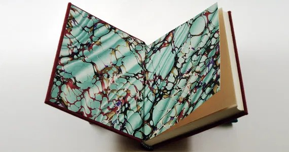 A hard-backed book is held open. Inside is blue and brown marbled paper.