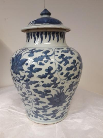 A baluster-shaped jar with a lid. The body has a blue design on white ground featuring a scrolling floral design. The flowers are probably peonies.