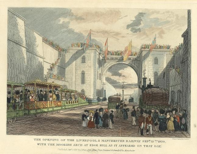 A busy scene. To the left are ornate coaches packed with people inside. The men wear black coats and top hats and the women are in colourful Victorian dress. In the foreground are more figures including uniformed soldiers with red jackets and tall, bearskinned hats. In the background is a large archway with towers either side. People are stood all along the parapet of this structure and flags hand