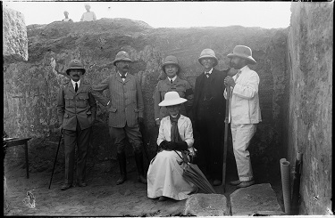 Photograph of a group visiting the excavations at Meroë, including (from left) Midwinter Bey, Director of Sudan Railways; General Herbert Kitchener, 1st Earl Kitchener; General Sir Francis Reginald Wingate, 1st Baronet, Governor-General of Sudan; Professor Archibald Sayce; John Garstang; and Lady Catherine